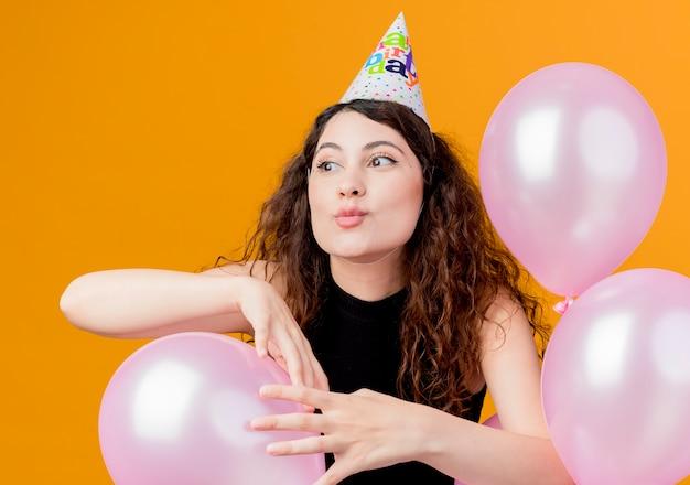 Jonge mooie vrouw met krullend haar in een vakantiepet met luchtballons het gelukkige en opgewekte concept van de verjaardagsfeestje die zich over oranje muur bevinden