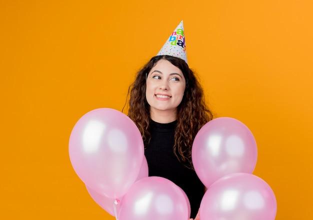Jonge mooie vrouw met krullend haar in een vakantiepet met luchtballons het gelukkige en opgewonden concept van de verjaardagsfeestje die zich over oranje muur bevinden