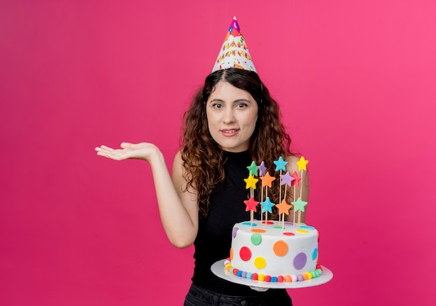 Jonge mooie vrouw met krullend haar in een vakantiepet met verjaardagstaart kijken verward schouderophalend schouders verjaardagsfeestje concept staande over roze muur