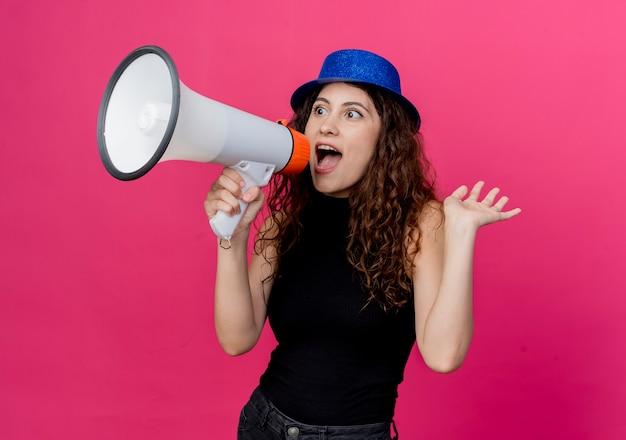 Jonge mooie vrouw met krullend haar in feestmuts die naar megafoon schreeuwt die gelukkig en opgewonden over roze muur staat