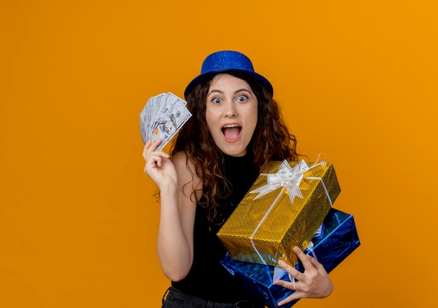 Jonge mooie vrouw met krullend haar in feestmuts met contant geld en geschenken kijken naar canera blij en opgewonden staande over oranje muur