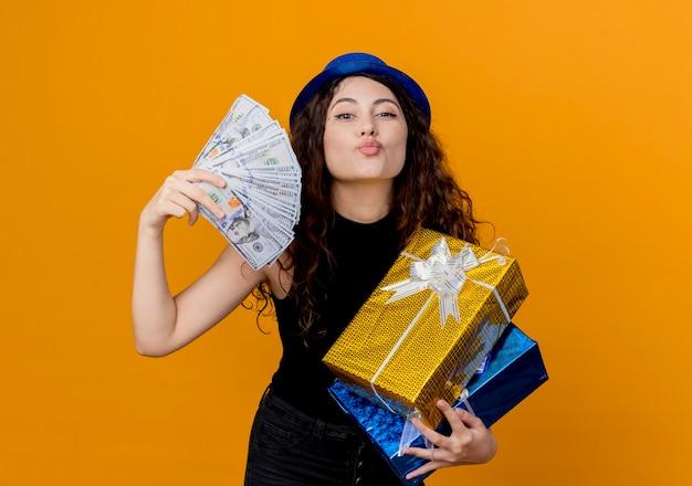 Jonge mooie vrouw met krullend haar in feestmuts met contant geld en geschenken kijken naar canera blij en vrolijk blaast een kus over oranje