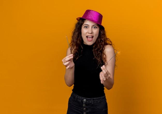 Jonge mooie vrouw met krullend haar in feestmuts met wonderkaarsen blij en opgewonden staande over oranje muur