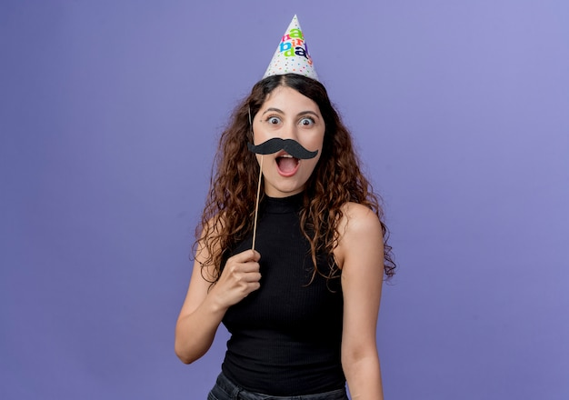 Jonge mooie vrouw met krullend haar in vakantie glb met snor partij stokken blij en verrast staande over blauwe muur