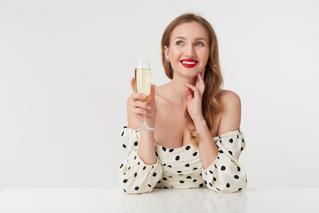 Jonge mooie vrouw met lang blond haar en rode lippen, vingert de kin en presenteert de aanstaande bruiloft en kijkt dromerig op. geïsoleerd op roze achtergrond.