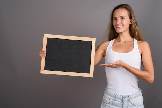 Jonge mooie vrouw met lang blond haar tegen een grijze achtergrond