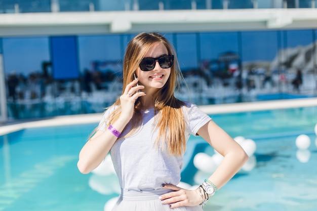 Jonge mooie vrouw met lang haar en in zwarte zonnebril staat dichtbij zwembad