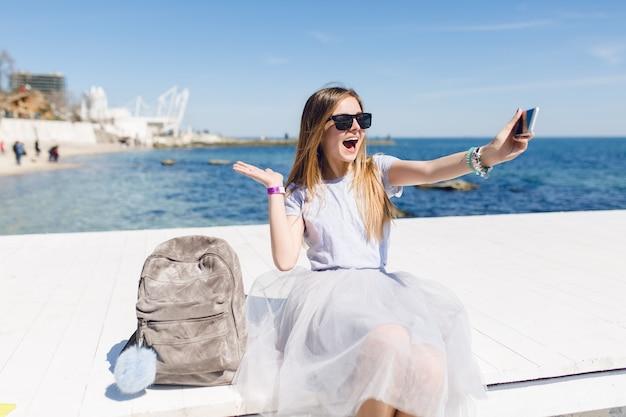 Jonge mooie vrouw met lang haar zit op de pier