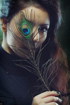 Jonge mooie vrouw met lang krullend haar die pauwenveer voor haar gezicht houdt, donkergroene achtergrond