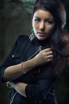 Jonge mooie vrouw met lang krullend haar op grungeachtergrond