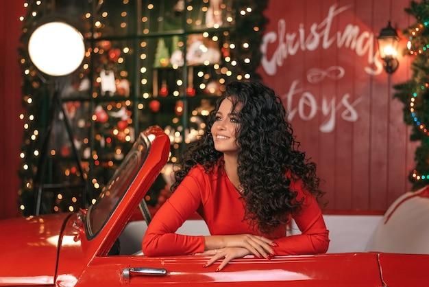 Jonge mooie vrouw met lang krullend haar poseren in een rode auto. nieuwjaars decor. slingers.