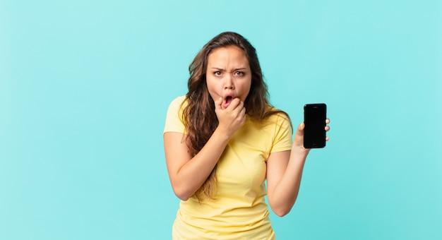 Jonge mooie vrouw met mond en ogen wijd open en hand op kin en met een slimme telefoon