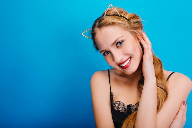 Jonge mooie vrouw met mooie glimlach, blauwe ogen, mooie huid, gevoelige blik, op feestje, poseren. stijlvolle hoofdband van kattenoor met diamanten.