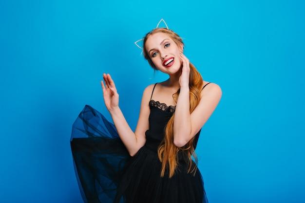 Jonge mooie vrouw met mooie glimlach, wapperende zwarte jurk, poseren. ze heeft lang haar, een hoofdband met kattenoren, mooie make-up met rode lippenstift.