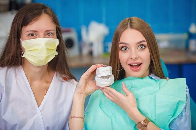 Jonge mooie vrouw met mooie witte tanden die op een tandstoel zitten en een plastic gebit in een doos houden.