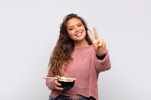 Jonge mooie vrouw met noedels die gelukkig, zorgeloos en positief glimlachen en kijken, overwinning of vrede met één hand gebaren