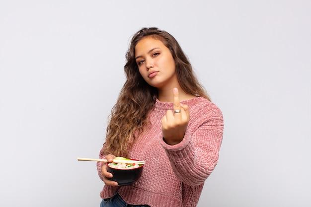 Jonge mooie vrouw met noedels die zich boos, geïrriteerd, opstandig en agressief voelt, de middelvinger omdraait, terugvecht
