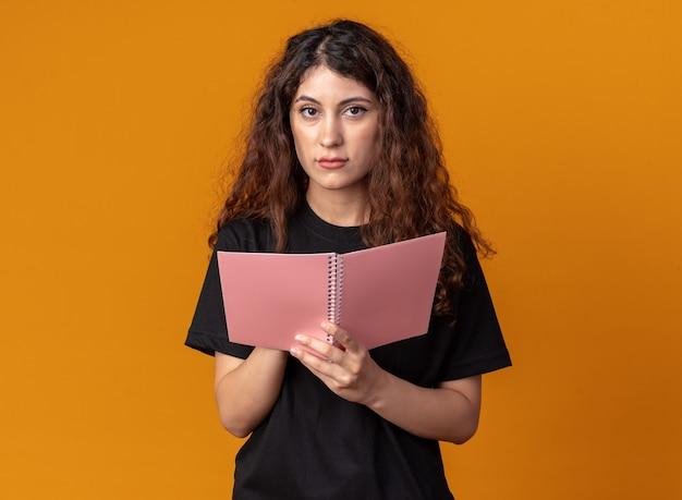 Jonge mooie vrouw met notitieblok kijkend naar de voorkant geïsoleerd op een oranje muur met kopieerruimte
