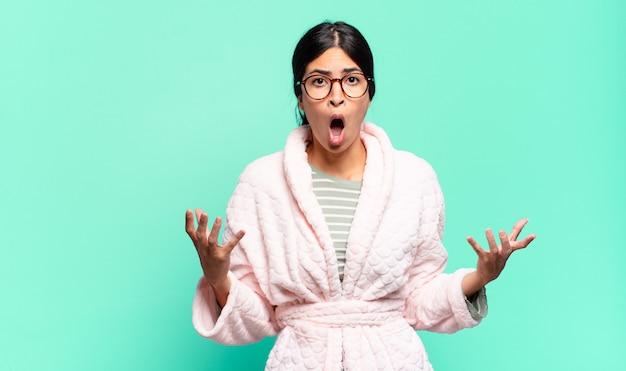 Jonge mooie vrouw met open mond en verbaasd, geschokt en verbaasd over een ongelooflijke verrassing. pyjama's concept