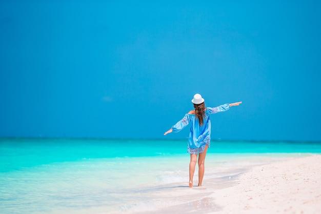 Jonge mooie vrouw met plezier op tropische kust. gelukkig meisje met blauwe lucht en turkoois water in de zee op het caribische eiland