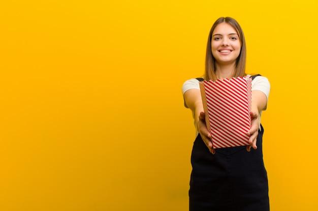 Jonge mooie vrouw met pop likdoorns tegen oranje achtergrond