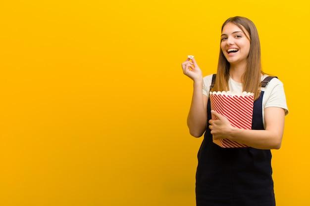 Jonge mooie vrouw met pop likdoorns tegen oranje muur