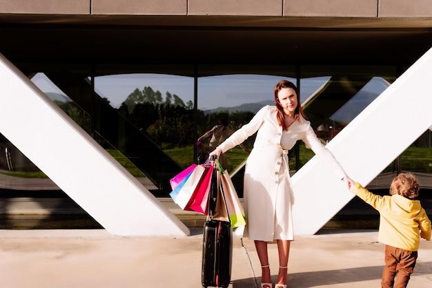 Jonge mooie vrouw met reiskoffer en boodschappentassen gesleept door haar 3-jarige zoon. ze shopaholic concept. familie reizen