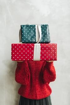 Jonge mooie vrouw met rode gebreide trui en grijze rok met grote handgemaakte geschenkdozen