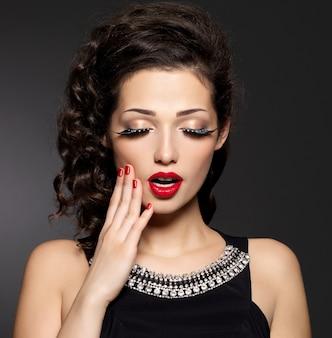 Jonge mooie vrouw met rode manicure, lippen en creatieve oogmake-up. mannequin met heldere uitdrukkingen