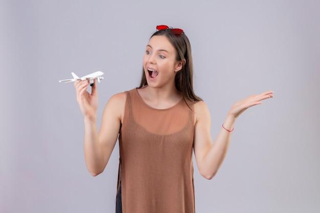 Jonge mooie vrouw met rode zonnebril op hoofd bedrijf speelgoed vliegtuig op zoek speels en gelukkig staan met arm opgeheven op witte achtergrond