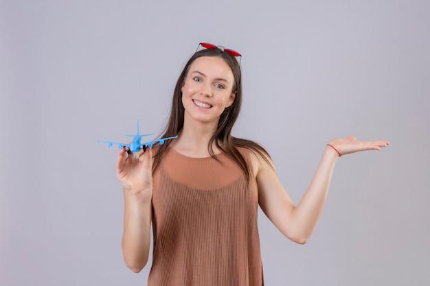 Jonge mooie vrouw met rode zonnebril op hoofd bedrijf speelgoed vliegtuig presenteren met arm van de hand lachend met blij gezicht staande op witte achtergrond