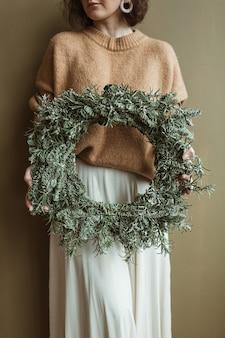Jonge mooie vrouw met ronde krans frame gemaakt van dennentakken tegen olijfmuur