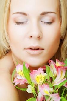 Jonge mooie vrouw met roze bloemen