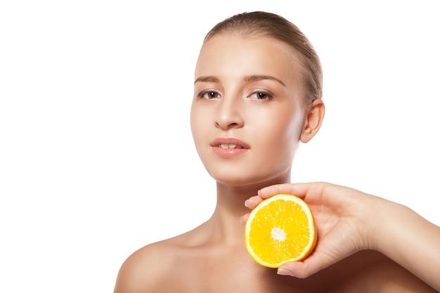 Jonge mooie vrouw met sinaasappel over wit