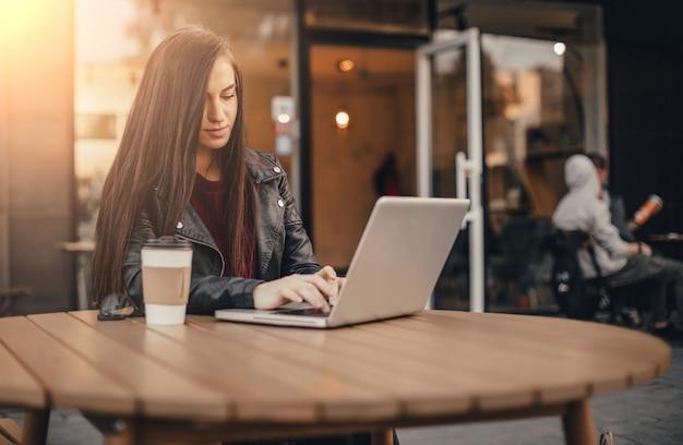 Jonge mooie vrouw met smartphone en kopje koffie zitten op straat in de stad