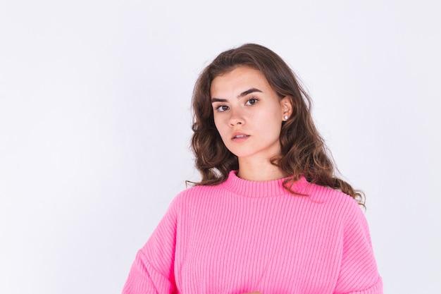 Jonge mooie vrouw met sproeten lichte make-up in trui op witte muur poseren