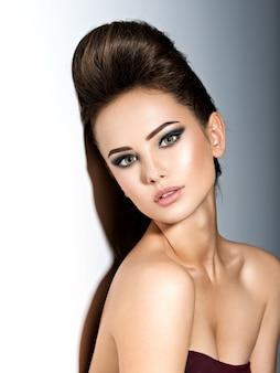 Jonge mooie vrouw met stijlvol kapsel poseren in studio over donkere achtergrond