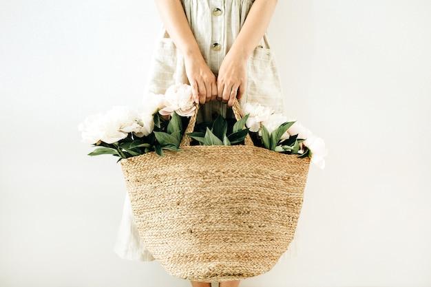 Jonge mooie vrouw met strozak met witte pioenroos bloemen op witte ondergrond