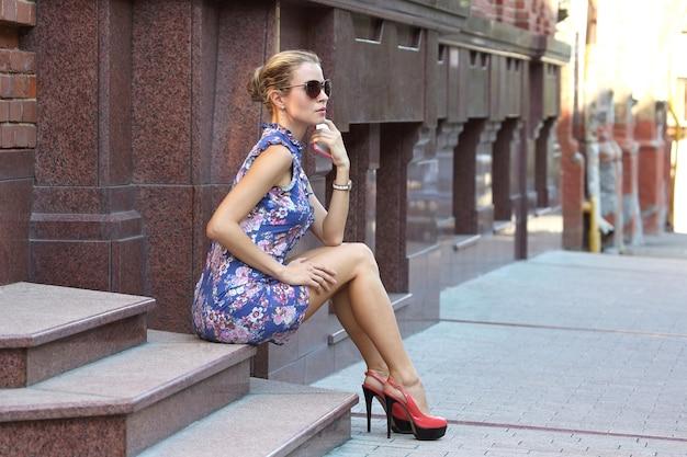 Jonge mooie vrouw met telefoon in hand zittend op de trap