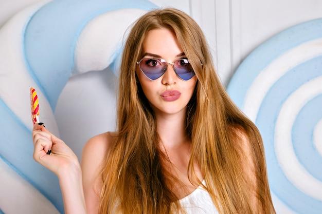Jonge mooie vrouw met verbazingwekkende lange haren likken grote lolly, zoete suiker dieetvoeding concept, schattige lipkleuren.