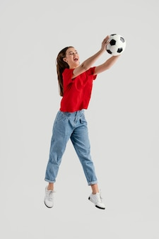 Jonge mooie vrouw met voetbalbal het springen Premium Foto