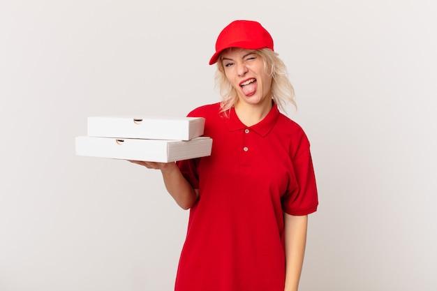Jonge mooie vrouw met vrolijke en opstandige houding, een grapje en tong uitsteekt. pizza bezorgconcept