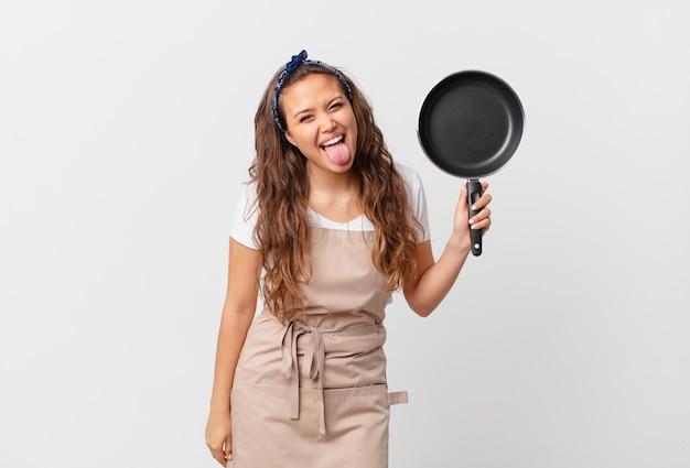 Jonge mooie vrouw met vrolijke en rebelse houding, grappen makend en tong uitsteken chef-kok concept en een pan vasthouden