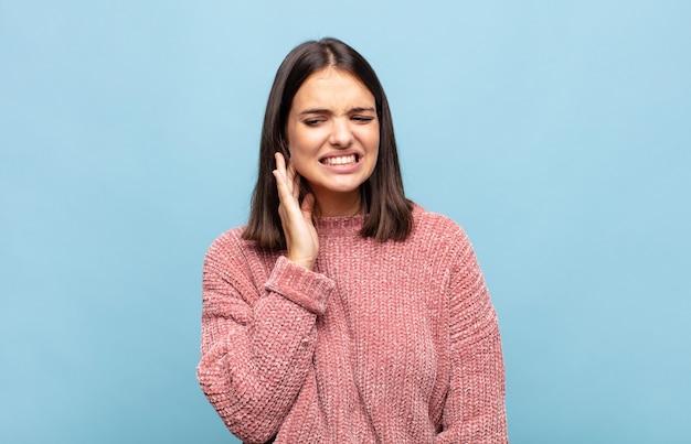 Jonge mooie vrouw met wang en pijnlijke kiespijn, zich ziek, ellendig en ongelukkig voelen, op zoek naar een tandarts