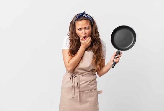 Jonge mooie vrouw met wijd open mond en ogen en hand op het concept van de kinchef-kok en een pan houden