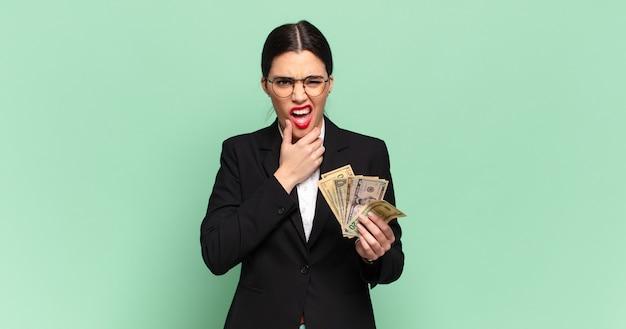 Jonge mooie vrouw met wijd open mond en ogen en hand op kin, onaangenaam geschokt, zeggend wat of wauw. zaken en bankbiljetten concept