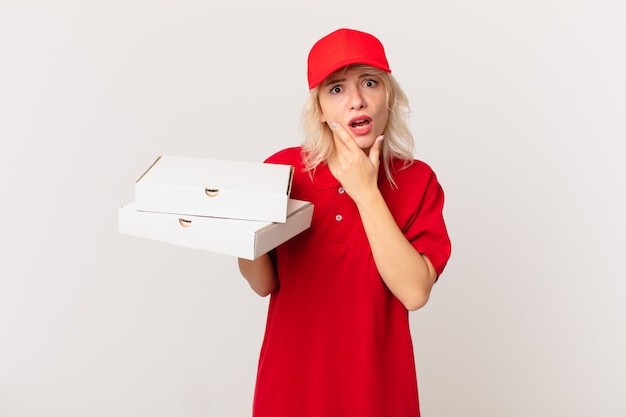 Jonge mooie vrouw met wijd open mond en ogen en hand op kin. pizza bezorgconcept