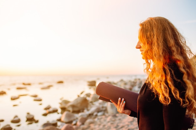Jonge mooie vrouw met yogamat die zich op strand in de zomer bij zonsondergang bevinden en klaar voor training.