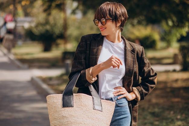 Jonge mooie vrouw met zak buiten de straat