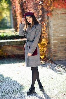 Jonge mooie vrouw met zeer lang haar die de winterlaag en glb op de achtergrond van de herfstbladeren dragen